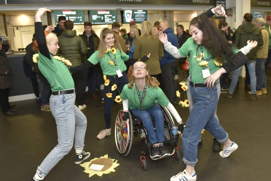 images of young dancers performing in green t-shirts and sunflower wreaths around their necks, during half time at a very busy rugby game